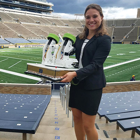 Engineering undergrad Cara Ravasio showing off a mechatronic football robot inside Notre Dame Stadium