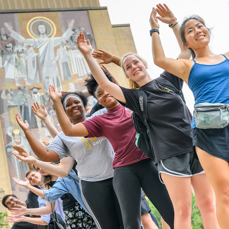 Graduate students participating in an orientation event in front of Hesburgh Library