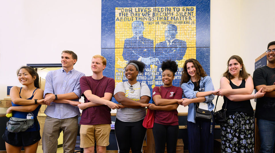 Grad students holding hands in front of mosaic of Dr. Martin Luther King, Jr. and Father Hesburgh
