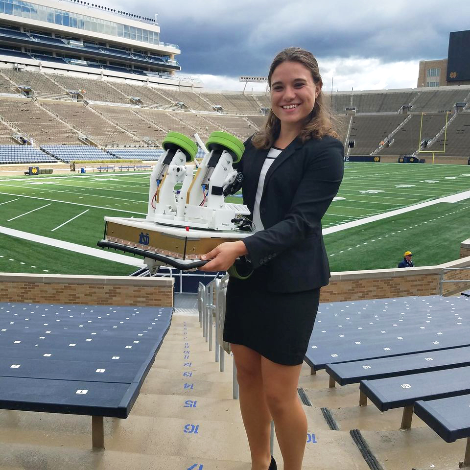 Engineering undergrad Cara Ravasio showing off a mechatronic football robot inside Notre Dame Stadium