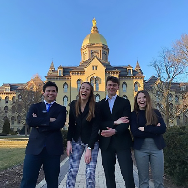 Notre Dame students standing together with Golden Dome in background