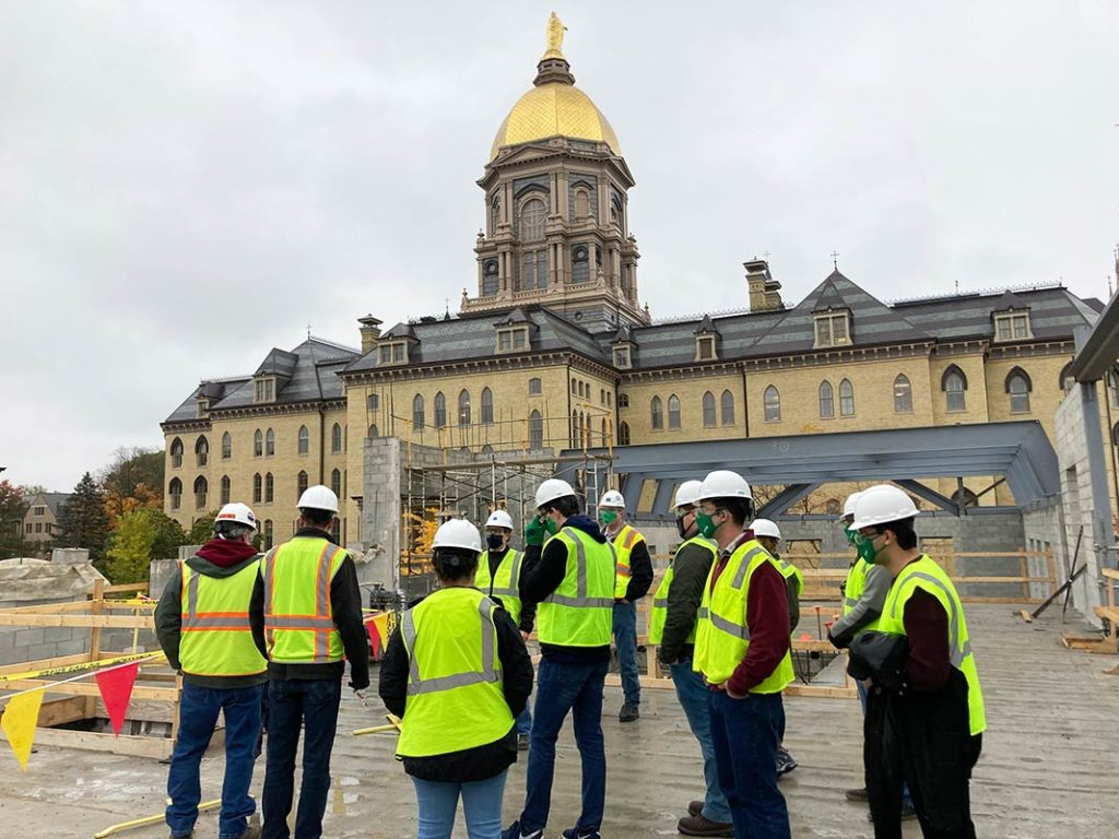 MEng students touring a construction site on campus to investigate the building's load-bearing masonry walls. The Golden Dome is in the background.