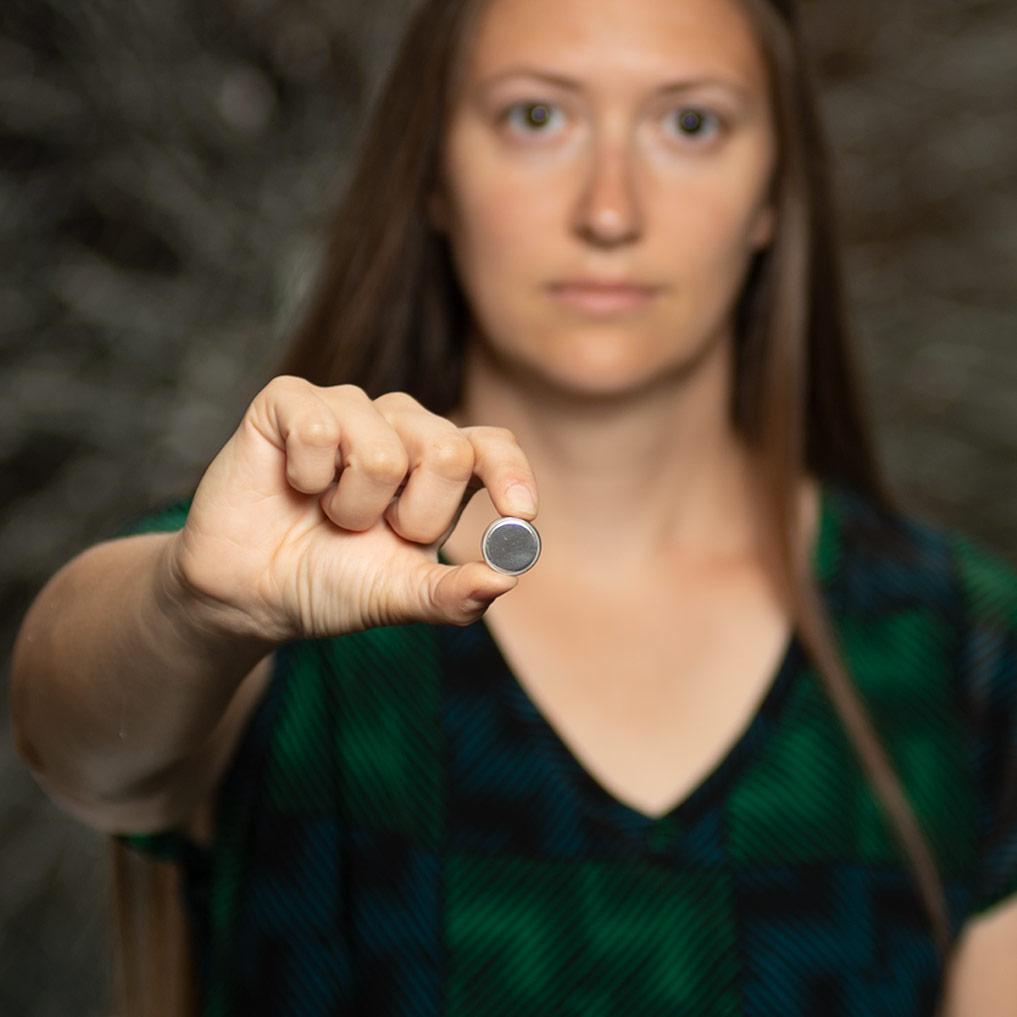 Prof. Jennifer Schaefer holding coin sized lithium ion battery